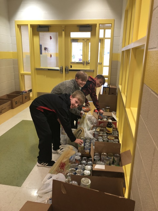Students adding items to our food drive.